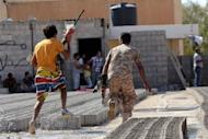 Libyan security forces dash for cover during clashes with protesters in Benghazi on June 8, 2013. Clashes between Libyan elite forces and gunmen killed six soldiers in Benghazi on Saturday, the army said, in the latest bout of unrest as the government struggles to control rebels from the 2011 uprising