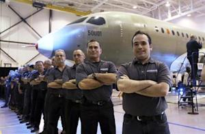 Bombardier employees form a line as the CS300 aircraft is unveiled at a news conference at its assembly facility in Mirabel, Quebec
