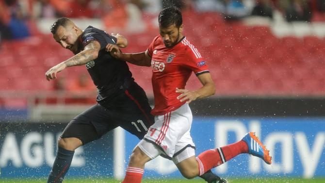 Olympiacos' Kostas Mitroglou, left, fights for the ball with Benfica's Ezequiel Garay during the Champions League group C soccer match between SL Benfica and Olympiacos FC in Lisbon, Wednesday, Oct. 23, 2013. The game ended in a 1-1 draw