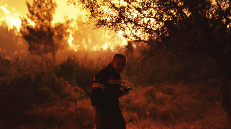 A firefighter walks by the flames of a burning forest fire in Varibobi, a northwestern suburb of Athens, Tuesday, Aug. 6, 2013. A large wildfire raged through the suburb burning about four houses. No injuries were reported. (AP Photo/Michail Michailidis)