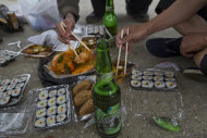 """In this June 16, 2014 photo, North Korean men share a picnic lunch and North Korean-brewed and bottled Taedonggang beer along the road in North Korea's North Hwanghae province. The Associated Press was granted to embark on a weeklong road trip across North Korea to the country's spiritual summit Mount Paektu. The trip was on North Korea's terms. An AP reporter and photographer couldn't interview ordinary people or wander off course, and government """"minders"""" accompanied them the entire way. (AP Photo/David Guttenfelder)"""