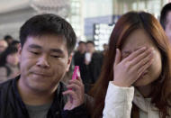 ALTERNATE CROP OF XHG102 A woman cries at the arrival hall of the International Airport in Beijing, China, Saturday, March 8, 2014. Relatives and friends were arriving at Beijing airport for news after a Malaysia Airlines Boeing 777-200 was reported missing on a flight from Kuala Lumpur to Beijing Saturday. (AP Photo/Ng Han Guan)