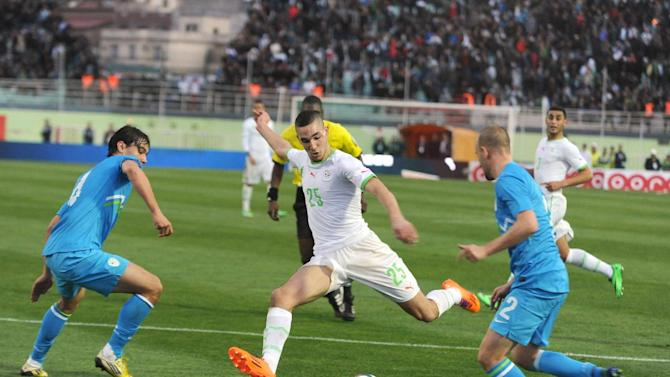 In this photo dated Wednesday, March 5, 2014, Algerian player, Nabil Bentaleb , center, attempts a shot while two unidentified Slovenian players look on during their international friendly match at Blida stadium, near the Algerian capital Algiers. Algeria defeated Slovenia 2-0