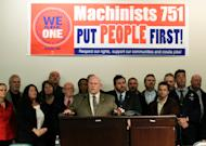Tom Wroblewski, center, president of Boeing Machinists Union District Lodge 751, announces Wednesday, Nov. 30, 2011, that the Boeing Co. and the Machinists union had reached a tentative agreement to build the new Boeing 737 MAX airplane in Renton, Wash., and enter into a new four-year labor contract. (AP Photo/Ted S. Warren)