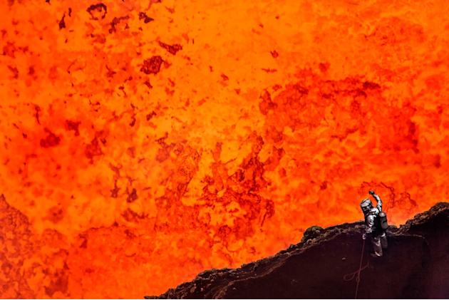 Geoff Mackley, wearing protective gear, looks down at 1,150 degree lava at the heart of the Marum Volvano, Vanuatu (Caters)