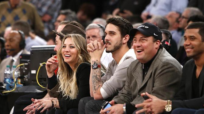 CORRECTS NAME TO KENNY DICHTER, CEO OF WHEELS UP, INSTEAD OF ACTOR STEVE SCHIRRIPA - From left, actress Kaley Kuoco, her husband, tennis player Ryan Sweeting, Wheels Up CEO Kenny Dichter and Seattle Seahawks quarterback Russell Wilson attend an NBA basketball game between the Dallas Mavericks and the New York Knicks, Monday, Feb. 24, 2014, in New York. Dallas won 110-108