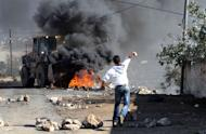 A Palestinian protester throws a stone at an Israeli bulldozer during a demonstration against the expropriation by Israel of the West Bank village of Kafr Qaddum, near Nablus, on November 30, 2012. Israel is to build 3000 new settler homes in east Jerusalem and the West Bank after the Palestinians won recognition as a non-member state at the United Nations