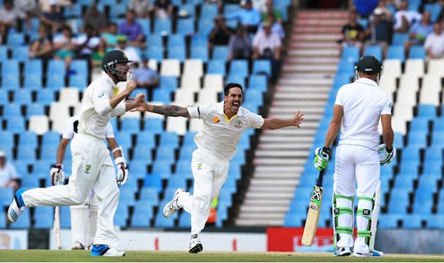 Australia's bowler Mitchell Johnson, center, with teammate reacts after dismissing South Africa's batsman Faf du Plessis, right, for 3 runs on the second day of their their cricket test match