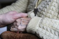 A woman, suffering from Alzheimer's desease, holds the hand of a relative in a retirement house in Angervilliers, eastern France. Alzheimer's disease causes two-thirds of dementia cases -- attacking one in 200 people -- and finding a cure has never been more pressing as the world's population grows and ages