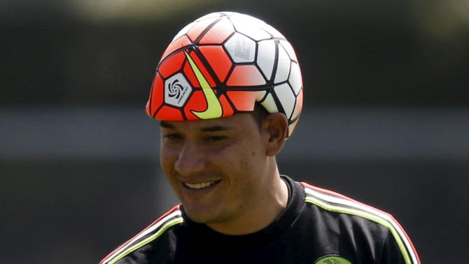 Mexico's goalkeeper Moises Munoz wears an uninflated ball over his head during a soccer training session in Mexico City