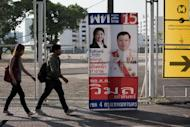People walk past Thai Prime Minister Yingluck Shinawatra's election campaign poster in Bangkok on January 31, 2014
