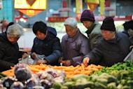 File photo of Chinese selecting vegetables at a food market in Huaibei, east China's Anhui province. China must implement deep reforms to avoid a sudden slowdown in growth, World Bank and Chinese government researchers said Monday