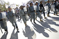 Afghan police officers walk in front of anti-Pakistan demonstrators during a rally, protesting against Pakistan's interference in Afghanistan, in Kabul, Afghanistan, Sunday, Oct. 2, 2011. (AP Photo/Kamran Jebreili)