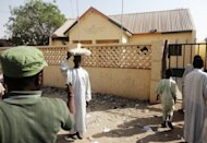 A street vendor passes by a partially burnt police station in the Sheka neighbourhood in Kano on January 25, 2012. Gunmen opened fire at a primary school in the northern Nigerian city of Kano on Tuesday, injuring four teachers before fleeing on a stolen motorcycle, police said.