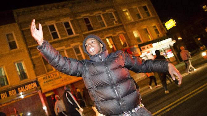 "A demonstrator signals to fellow marchers as they take to the street following a vigil held for Kimani ""Kiki"" Gray in the East Flatbush neighborhood of New York's Brooklyn borough, Wednesday, March 13, 2013, in New York. According to the NYPD, the teen pointed a .38-caliber revolver at the plainclothes officers, who responded by shooting him to death. (AP Photo/John Minchillo)"