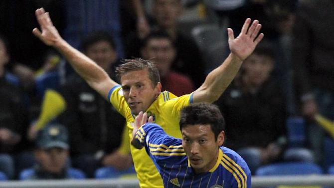 Kazakhstan's Maksat Baizhanov, front, and Sweden's Anders Svensson fight for the ball during their World Cup group C qualifying soccer match in Astana, Kazakhstan, Tuesday, Sept. 10, 2013. (AP Photo)