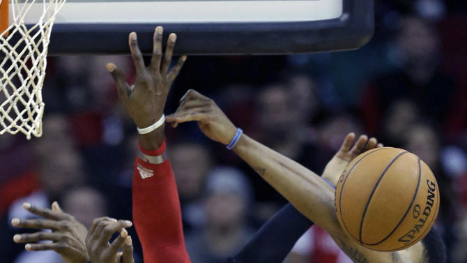 Houston Rockets' Dwight Howard, center, reacts after being fouled as Golden State Warriors' Kent Bazemore, right, and Jermaine O'Neal, left, defend during the first quarter of an NBA basketball game Friday, Dec. 6, 2013, in Houston