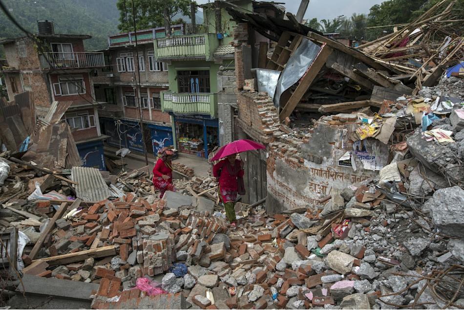 Local residents walk past collapsed houses after the April 25 earthquake, at Lamosangu village in Sindhupalchowk