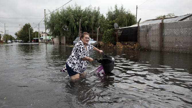 A woman pushes her bike through a flooded street in La Plata, in Argentina's Buenos Aires province, Wednesday, April 3, 2013. At least 35 people were killed by flooding overnight in Argentina's Buenos Aires province, the governor said Wednesday, bringing the overall death toll from days of torrential rains to at least 41 and leaving large stretches of the provincial capital under water. (AP Photo/Natacha Pisarenko)