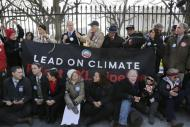 Civil rights activist Julian Bond (top row, 3rd L), Sierra Club Executive Director Michael Brune (top row, 4th L), and activists opposed to the Keystone XL tar sands pipeline project tie themselves to the White House fence during an environmental protest in Washington, February 13, 2013. REUTERS/Jonathan Ernst