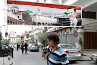 "A man walks under a banner depicting Syrian President Bashar al-Assad as he crosses a road in old Damascus on April 30. The Syrian authorities have set a deadline of 15 days for people who had committed ""unlawful acts"" to give themselves up, as a wave of arrests was reported across the country"