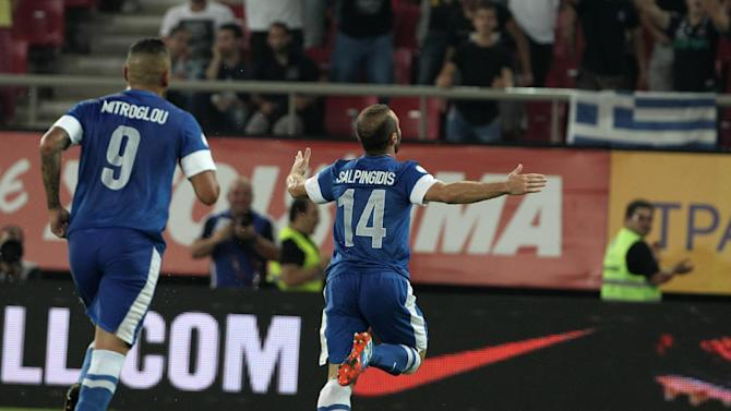Greece's Dimitris Salpingidis, right, celebrates scoring against Latvia during their World Cup Group G qualifying soccer match at the Karaiskaki stadium in Piraeus port, near Athens, on Tuesday, Sept. 10, 2013. Greece won 1-0