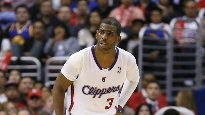 Los Angeles Clippers' Chris Paul holds his side after colliding with Golden State Warriors' Draymond Green during the second half of an NBA basketball game in Los Angeles, Wednesday, March 12, 2014. The Clippers won 111-98