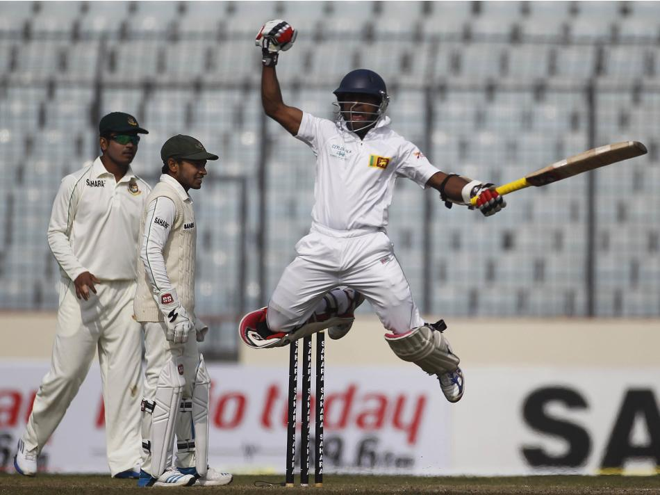 Sri Lanka's Silva celebrates after scoring a century as Bangladesh's Rahim and Rahman watch during their second day of first test cricket match of the series in Dhaka