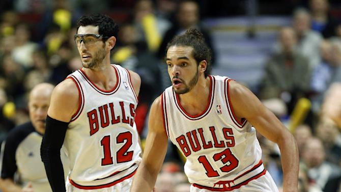 Chicago Bulls center Joakim Noah (13) runs a fast break in front of Chicago Bulls guard Kirk Hinrich (12) against the Miami Heat during the second half of an NBA basketball game in Chicago, Thursday, Dec. 5, 2013. The Bulls defeated the Heat 107-87