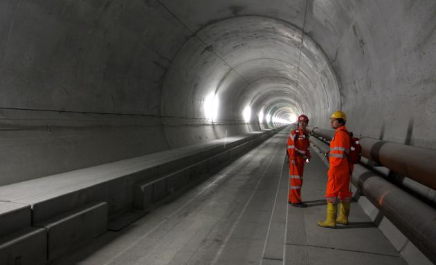An employee of AlpTransit Gotthard Ltd and a visitor stand at the NEAT Gotthard Base tunnel near Erstfeld
