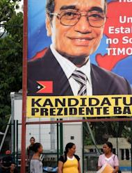 "Local residents are seen standing in front of a banner of presidential candidate Francisco ""Lu Olo"" Guterres in Dili. Former military commander Taur Matan Ruak was ahead in an early count for East Timor's presidential run-off vote on Monday, according to the elections secretariat"
