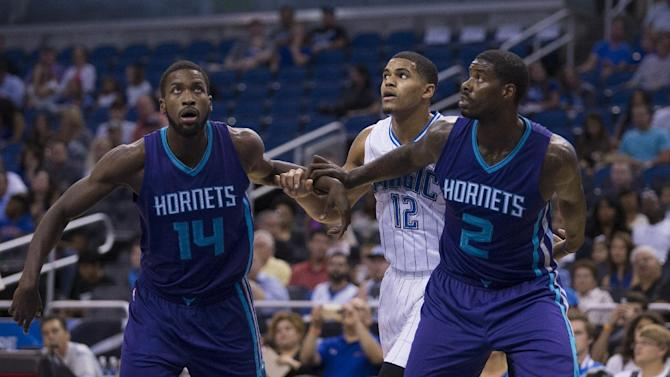 Charlotte Hornets forward Michael Kidd-Gilchrist (14) and teammate Charlotte Hornets forward Marvin Williams (2) box out Orlando Magic forward Tobias Harris (12) during the first half of an NBA basketball game in Orlando, Fla., Saturday, Oct. 3, 2015. Kidd-Gilchrist is expected to miss an extended period of time after an MRI revealed he has a torn labrum in his right shoulder.(AP Photo/Willie J. Allen Jr.)