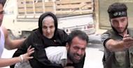 "An image grab taken from AFPTV on August 7 shows a man evacuating an old Syrian woman from her house during clashes between rebel fighters and Syrian government forces in the Bustan al-Qasr district of the northern Syrian city of Aleppo. President Bashar al-Assad vowed on Tuesday to crush the 17-month rebellion against his regime and to cleanse Syria of ""terrorists."""