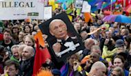 People protest against Russian President Vladimir Putin's visit to Amsterdam on April 8, 2013, with rainbow flags flying at half-mast around the city that prides itself on enjoying every kind of freedom