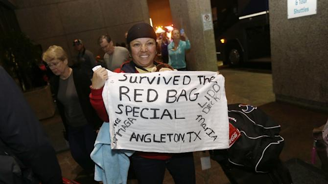 Veronica Arriaga, of Angleton, Texas, a passenger from the disabled Carnival Triumph cruise ship, holds a sign referring to the red biohazard bags used as toilets, after arriving by bus at the Hilton Riverside Hotel in New Orleans, Friday, Feb. 15, 2013. The ship had been idled for nearly a week in the Gulf of Mexico following an engine room fire. (AP Photo/Gerald Herbert)