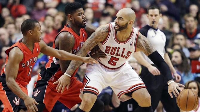 Chicago Bulls forward Carlos Boozer, right, controls the ball as Toronto Raptors forward Amir Johnson, center, and guard Kyle Lowry guard during the first half of an NBA basketball game in Chicago on Saturday, Dec. 14, 2013