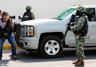 """Members of the Mexican Navy stand guard during an operation to present Mexican drug trafficker Joaquin Guzman Loera aka """"el Chapo Guzman"""" to the press, on February 22, 2014 in Mexico City"""