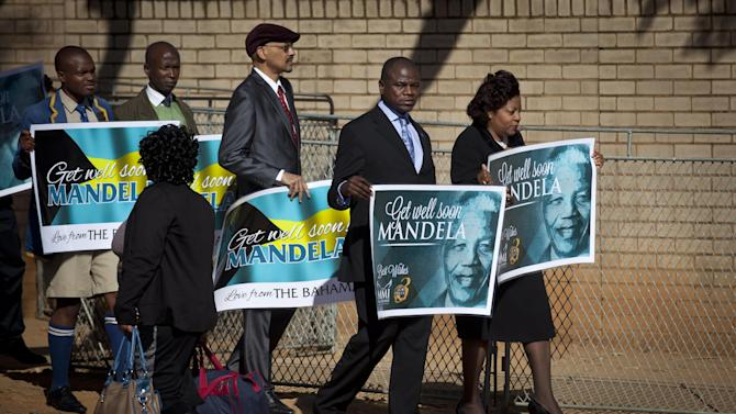 A group of wellwishers carrying get-well placards arrive at the Mediclinic Heart Hospital where former South African President Nelson Mandela is being treated in Pretoria, South Africa, Sunday, June 16, 2013. South Africa's president says that Nelson Mandela is seeing sustained improvement from the recurring lung infection that is forcing him to spend a ninth day in the hospital. (AP Photo/Ben Curtis)