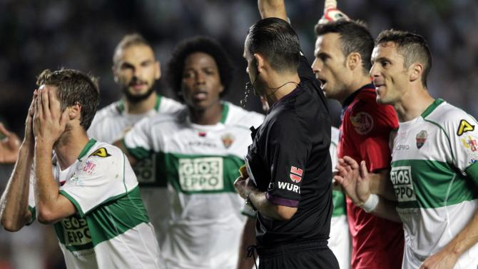 Elche's players protest as referee Muniz shows a yellow card to Perez during their Spanish first division match against Real Madrid in Elche
