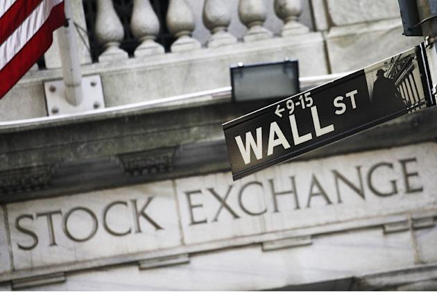 FILE - This July 16, 2013 file photo shows a Wall Street street sign outside the New York Stock Exchange in New York. U.S. stocks are starting the week sharply higher Monday, March 30, 2015, led by en