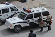 Two Tibetan Buddhist pilgrims look at a police car outside the Labrang Monastery in Xiahe, Gansu Province. China has ramped up security in Tibetan areas, rights groups and residents said after new self-immolation protests belied boasts of national unity at a key Communist Party congress in Beijing