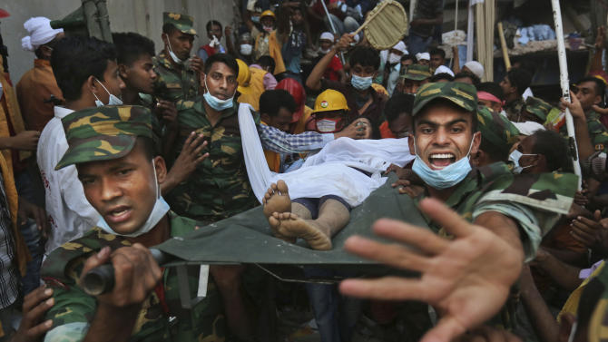 Bangladesh soldiers carry a woman survivor from the rubble at the site of a building that collapsed Wednesday in Savar, near Dhaka, Bangladesh, Thursday, April 25, 2013. By Thursday, the death toll reached at least 194 people as rescuers continued to search for injured and missing, after a huge section of an eight-story building that housed several garment factories splintered into a pile of concrete.(AP Photo/Kevin Frayer)