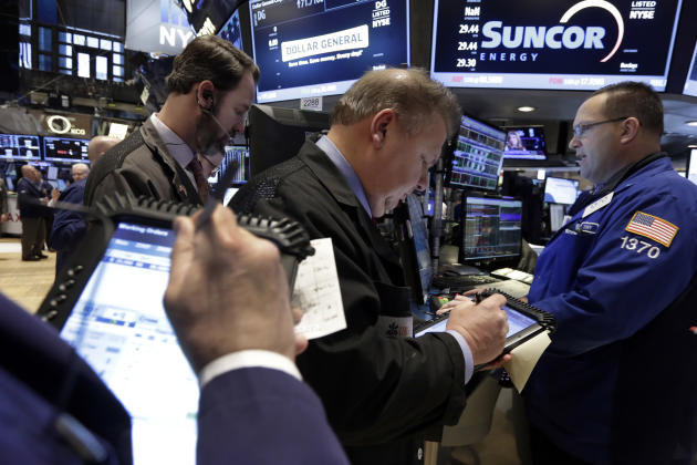 Traders gather at the post of specialist Anthony Matesic, right, on the floor of the New York Stock Exchange, Friday, March 6, 2015. Stocks opened lower on Friday as another strong U.S. jobs report ra