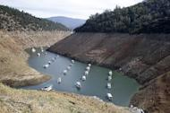 FILE - In this file photo taken Thursday, Oct. 30, 2014, houseboats sit in the drought lowered waters of Oroville Lake, near Oroville, Calif. Water levels dropped Monday, Feb. 13, 2017, at California's Lake Oroville, stopping water from spilling over a massive dam's potentially hazardous emergency spillway after authorities ordered the evacuation of people from towns lying below the lake. Lake Oroville also serves as a reservoir and levels rose significantly in recent weeks after a series of storms that have dumped rain and snow across California. (AP Photo/Rich Pedroncelli, File)