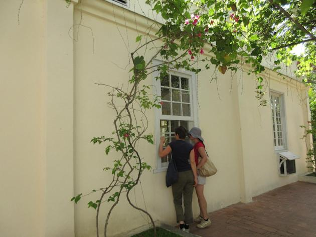 In this May 15, 2015 photo, two American tourists peer in through a windows of Ernest Hemingway's Havana home, Finca Vigia. The visitors, who would only give their names as Sabine and Anna, traveled t