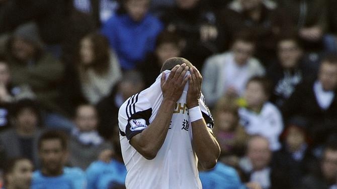 Swansea City's captain Ashley Williams hides his head in his shirt after Tottenham Hotspur scored their first goal during their English Premier League soccer match at the Liberty Stadium in Swansea