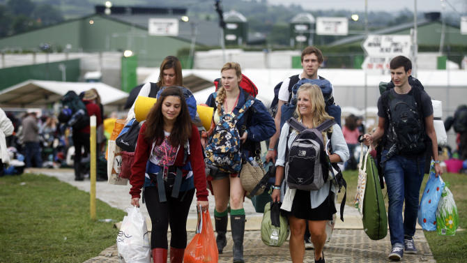 Festival goers arrive at the Glastonbury Music Festival site at Glastonbury England Wednesday, June 26, 2013. Thousands are to arrive for the three day festival that starts on Friday, June 28 2013 with headliners, Arctic Monkeys, the Rolling Stones and Mumford and Sons. (Photo by Jim Ross/Invision/AP)