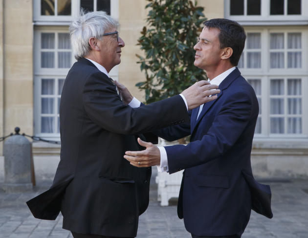 European Commission President Jean-Claude Juncker, left, is welcomed by French Prime Minister Manuel Valls, right, at the Hotel Matignon in Paris, France, Tuesday, Sept. 29, 2015. French Prime Ministe
