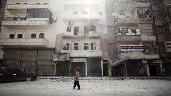 A Syrian man walks in front of a building destroyed by government shelling in Aleppo, Syria, Tuesday, Sept. 11, 2012. (AP Photo/Muhammed Muheisen)