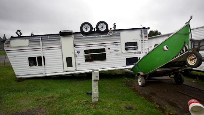 A camp trailer is left upside down at the Old Mill Marina trailer park in Garibaldi, Ore., after high winds and rain hit the Oregon coast on Monday, Nov. 19, 2012. The trailer was unoccupied when it flipped. Residents in Washington and Oregon are bracing for expected river flooding after heavy rain and winds that caused sporadic road closures, power outages and at least one death. The wet weather is expected to continue throughout the week, after hurricane-strength winds battered both states along the coast. (AP Photo/The Oregonian, Randy L. Rasmussen)  MAGS OUT; TV OUT; LOCAL TV OUT; LOCAL INTERNET OUT; THE MERCURY OUT; WILLAMETTE WEEK OUT; PAMPLIN MEDIA GROUP OUT